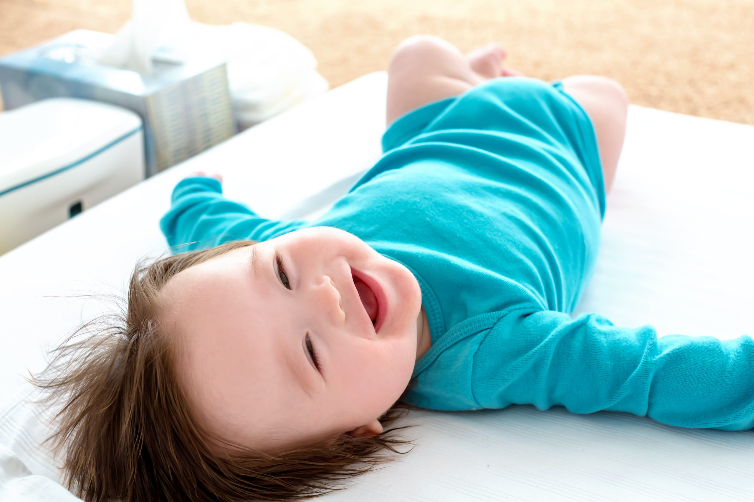 smiling baby boy on changing mat