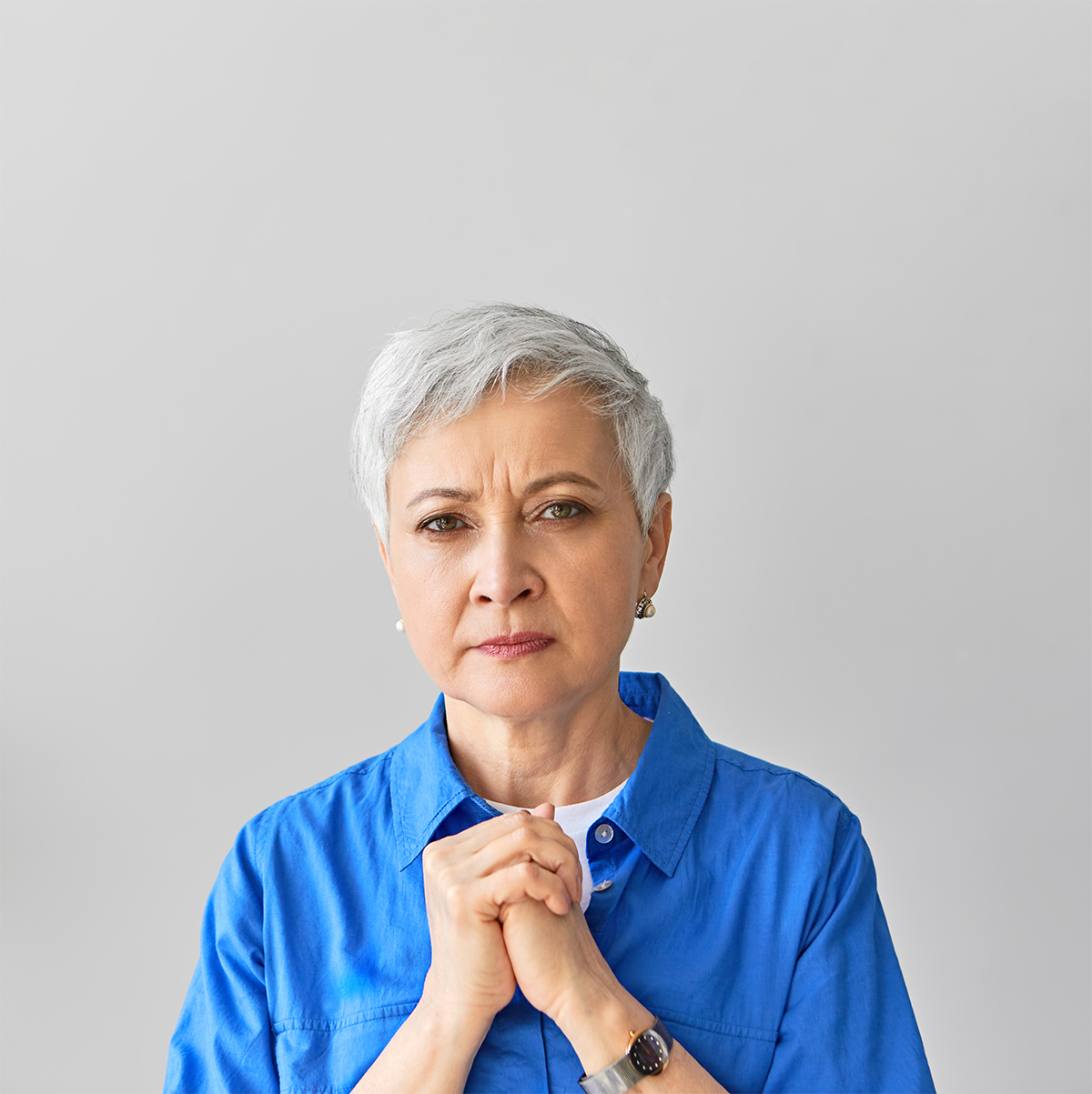 worried mature gray haired female clasping hands to chest